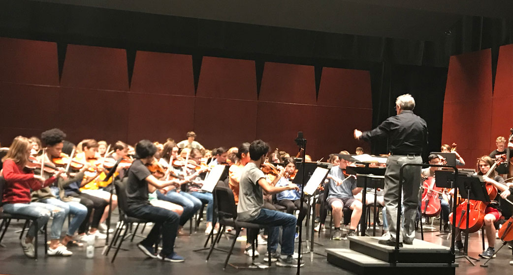 picture of the greenville county youth orchestra practicing on stage before a performance